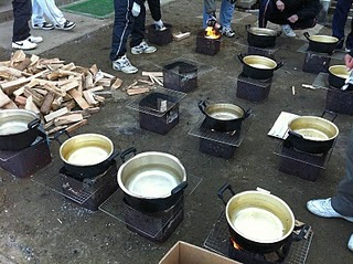 Ng and his fellow teachers prepare pots of boiling water outdoors to cook rice for those staying at the school.